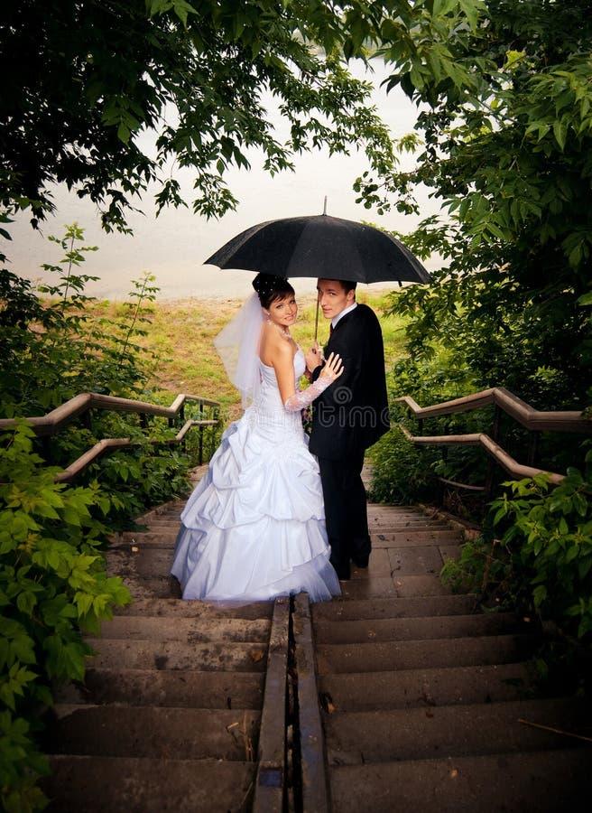 La mariée et le marié ont regardé en arrière en bas des escaliers images stock