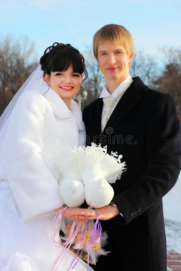 La mariée et le marié retiennent des paires de colombes blanches photographie stock libre de droits