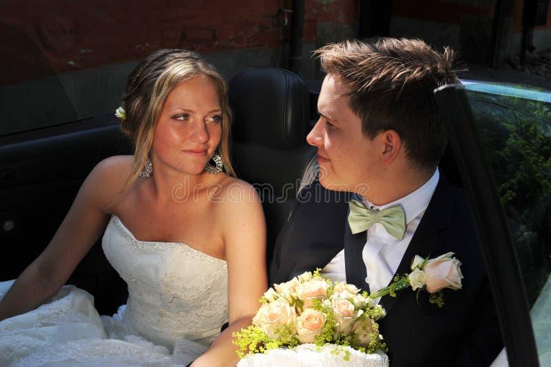 La mariée regarde affectueusement le marié. photographie stock