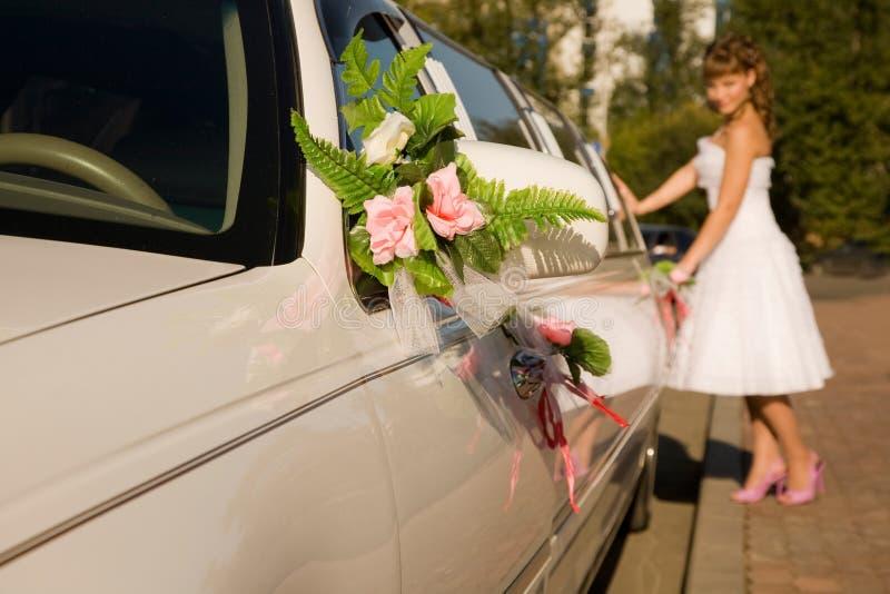 La mariée se tient prêt le véhicule de limousine photographie stock