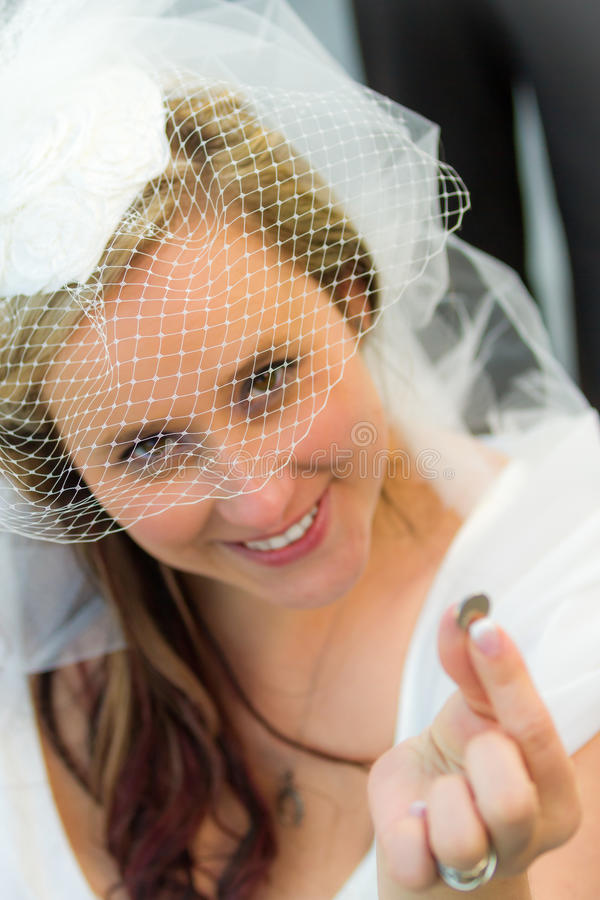 La mariée trouvent une pièce de monnaie chanceuse image libre de droits