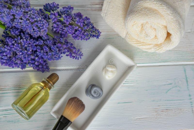 La mascarilla, friega y cepilla para el uso con las flores en un fondo de madera Concepto del balneario Visi?n desde arriba imagen de archivo