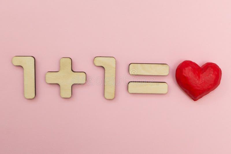 La matematica di amore Uno più uno uguaglia il cuore immagini stock