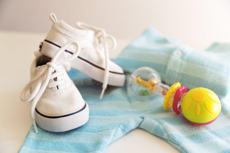 La materia del bebé está en un fondo blanco Cosas para el niño pequeño, ratt imagen de archivo