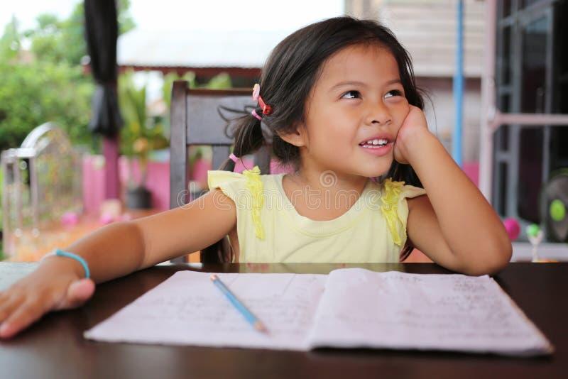 La matita asiatica di uso della ragazza del bambino scrive le lettere sul libro immagini stock libere da diritti