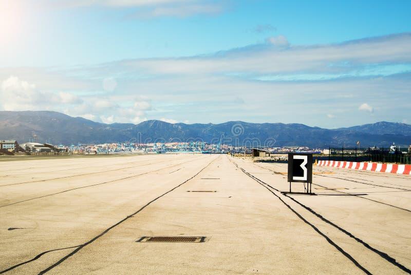 La mattina con giù espone al sole le luci alla pista dell'aeroporto di Gibilterra, delle montagne e del porto di Algesiras immagini stock libere da diritti