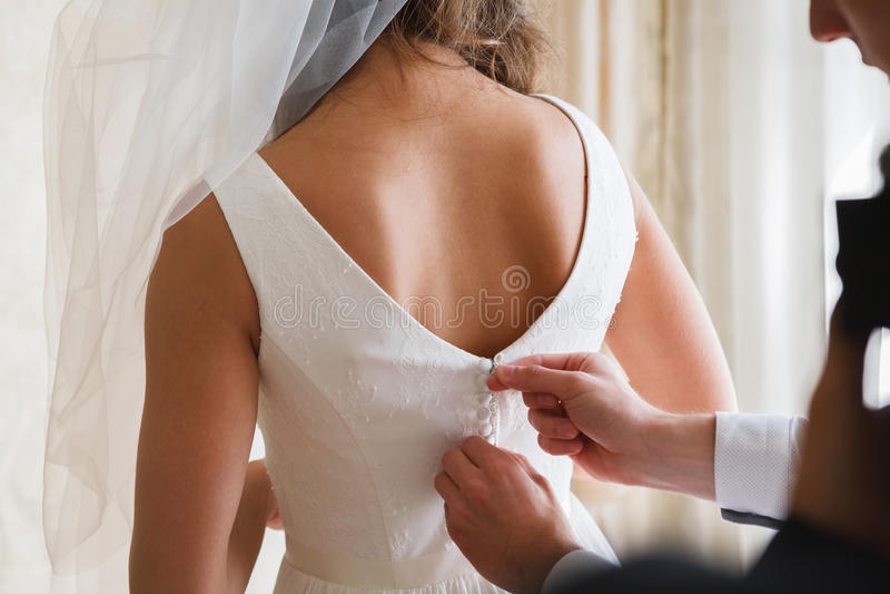 La mattina nuziale, sposa porta il vestito, retrovisione fotografia stock libera da diritti