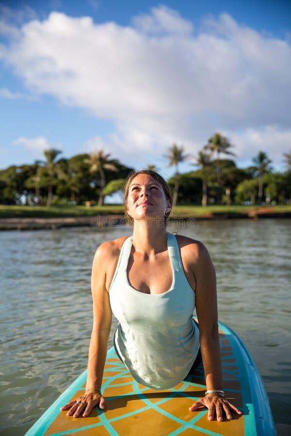 La mattina soleggiata risolve una giovane donna graziosa nell'yoga d ascendente del SUP fotografia stock