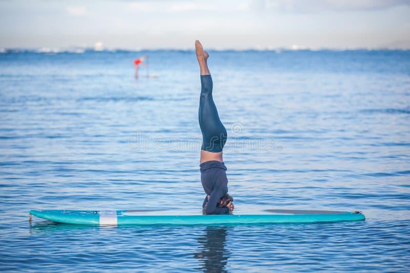 La mattina soleggiata risolve una giovane donna graziosa nella pratica di yoga del SUP fotografia stock libera da diritti