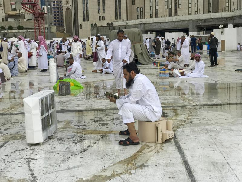 LA MECA, LA ARABIA SAUDITA - 29 DE MAYO DE 2019: Un hombre no identificado lee Quran después de un piso de las fuertes lluvias en fotos de archivo libres de regalías