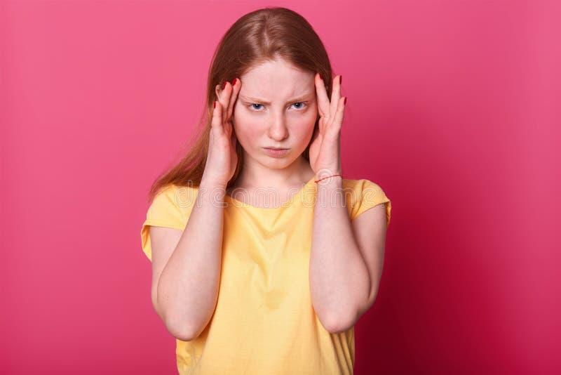 La media foto de la longitud de la muchacha adolescente triste con dolor de cabeza terrible, tiene problemas graves en escuela, l foto de archivo