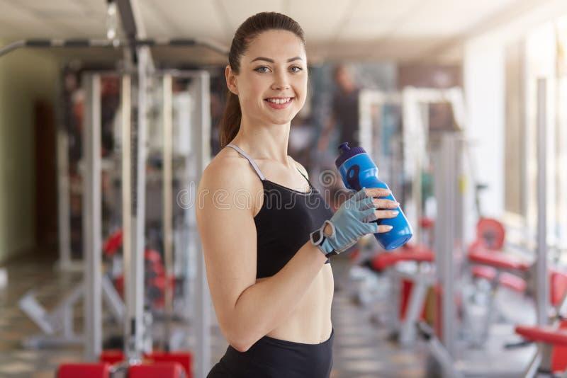 La media longitud tirada de mujer atlética con la botella azul a disposición, lleva el uniforme negro del deporte, tiene cola d imagen de archivo libre de regalías