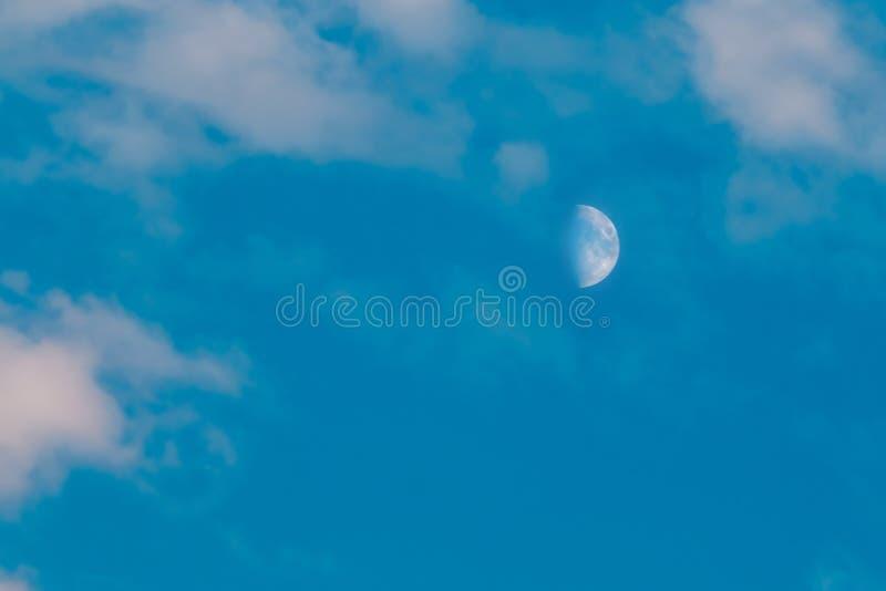 La media luna se ve en d3ia, en cielo azul con las nubes wispy fotografía de archivo libre de regalías