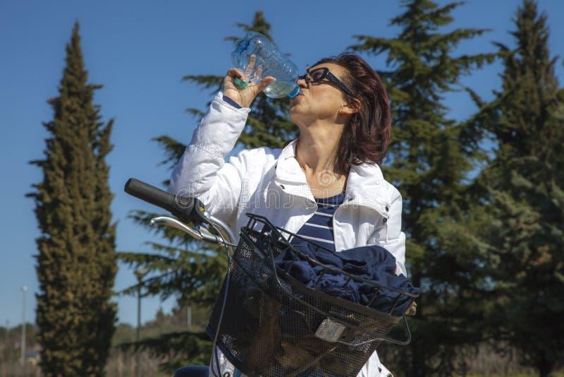Mediados de mujer sana envejecida con la botella de agua en la bici de montaña imagenes de archivo