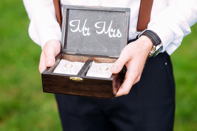 La mejor caja de la tenencia del hombre con los anillos de bodas de oro fotos de archivo libres de regalías