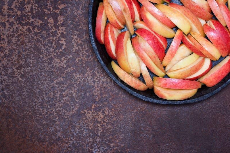 La mela ha tagliato dai pezzi in una padella nera della ghisa su una superficie di metallo arrugginita Preparazione per la torta  fotografia stock