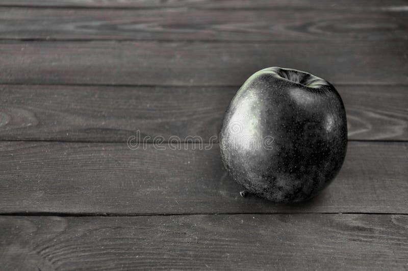 La mela nera si trova su una tavola di legno grigia contro fotografia stock