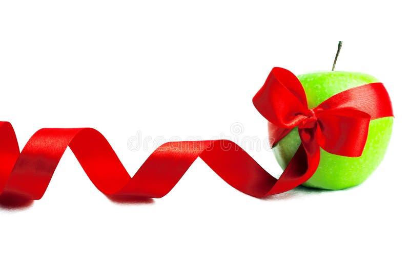 La mela verde è colore rosso decorato da un nastro fotografia stock