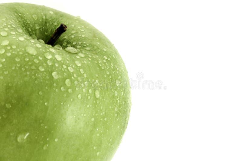 La mela verde con il primo piano delle goccioline di acqua ha sparato su bianco con lo spazio della copia per testo fotografia stock
