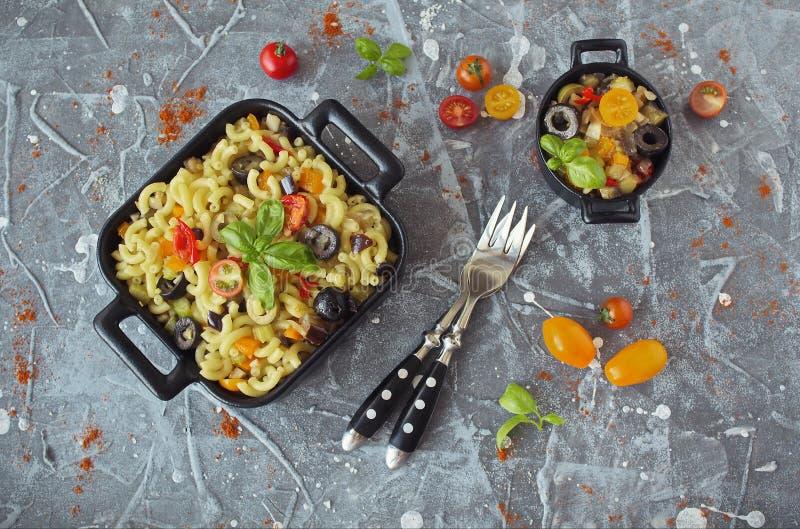 La melanzana, le olive ed il pomodoro sgomitano la pasta dei maccheroni, su un vassoio nero del servizio fotografia stock