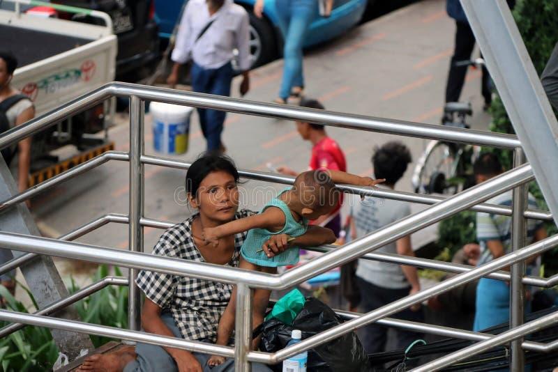 La mendiante de mère et de bébé sur la passerelle à la jonction croisent entre Anawrahta Rd et Sule Pagoda Rd images libres de droits