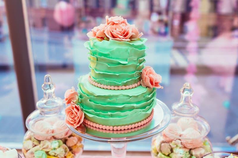 la menta Due-livellata ha colorato la torta nunziale con le rose e i macarons crema su fondo della vetrina di vetro immagini stock