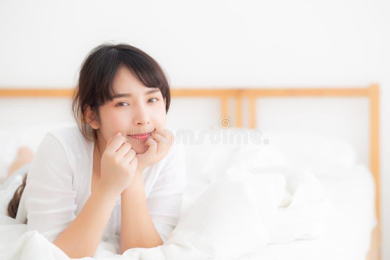 La mentira de la mujer del retrato hermoso y el rato asiáticos jovenes de la sonrisa despiertan con salida del sol en la mañana,  imagen de archivo
