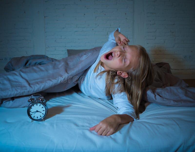 La mentira de la niña despierta en medio de la noche desordenes durmientes del sufrimiento cansado y agitado imagen de archivo libre de regalías