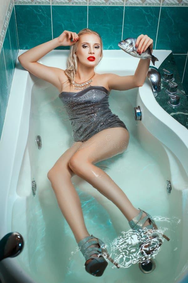 La mentira hermosa de la mujer se vistió en una bañera y los pescados el sostenerse imagen de archivo