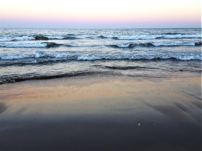 La mer bleue de coucher du soleil ondule la plage photo stock