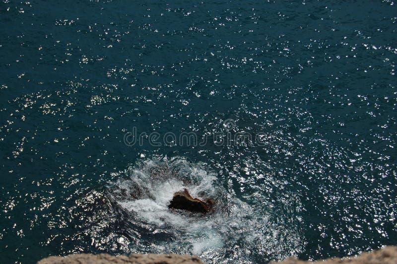 La mer bleue est évidente des roches photos stock
