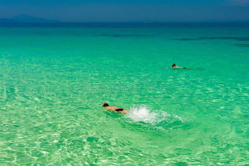 La mer clair comme de l'eau de roche de turquoise avec l'homme font presque naviguer au schnorchel dans l'eau photos stock