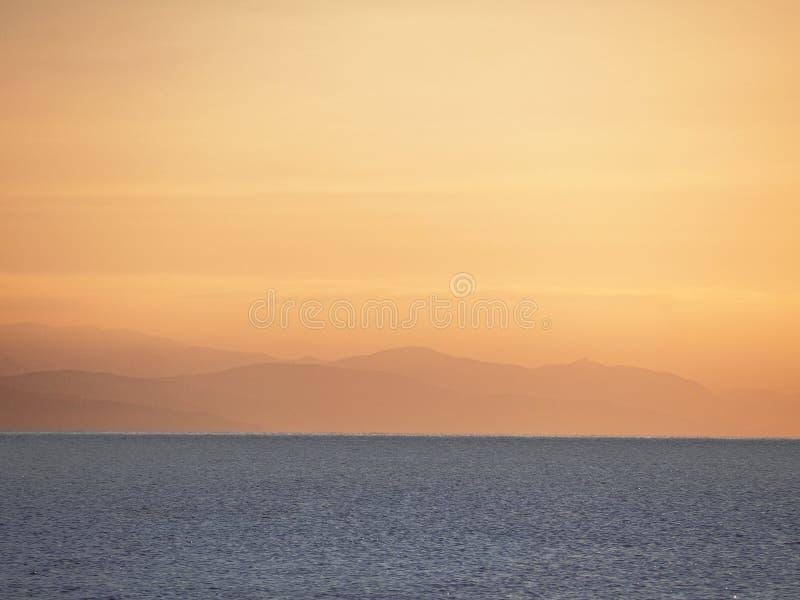 La mer et les montagnes pendant le lever de soleil images stock