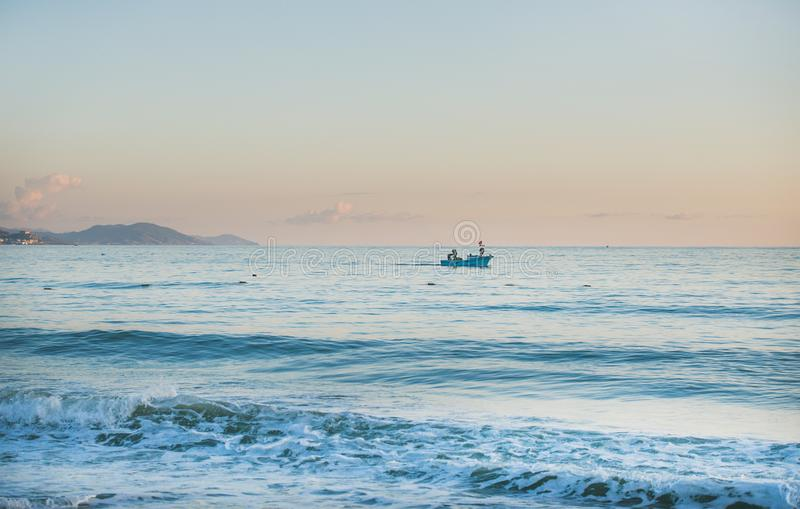 La mer Méditerranée et bateau calmes au coucher du soleil, couleurs en pastel photos libres de droits