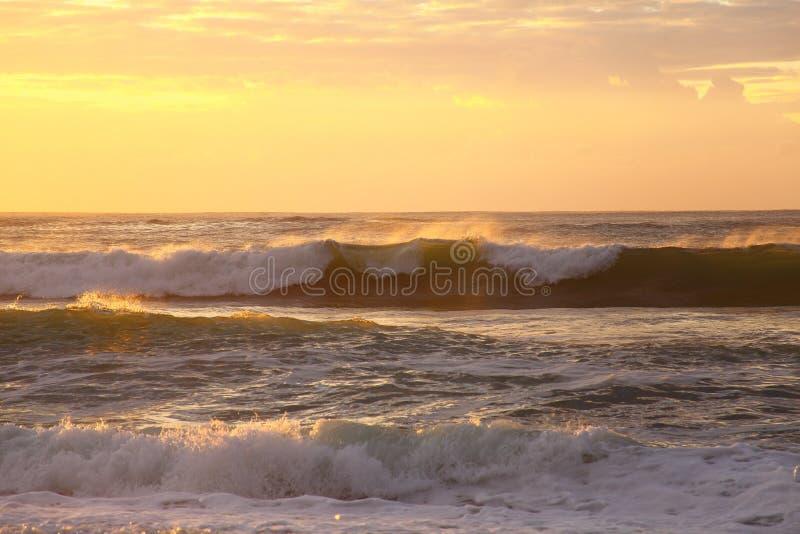 La mer ondule le roulement par lever de soleil d'or images stock