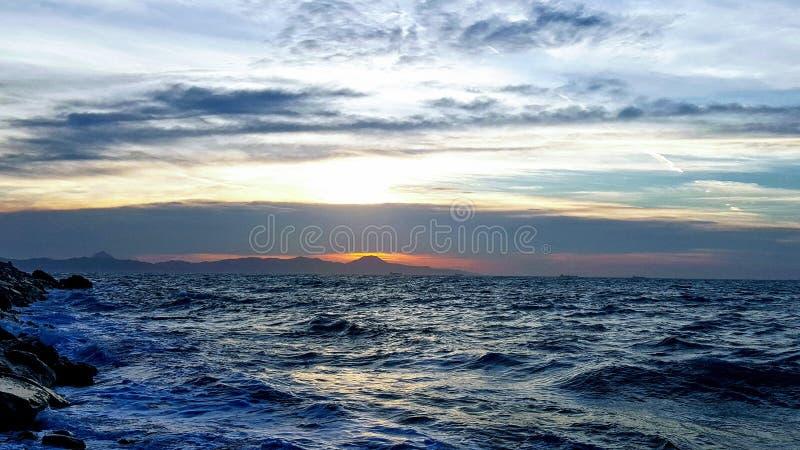 La mer semble le ciel fâché avec le coucher du soleil derrière image libre de droits