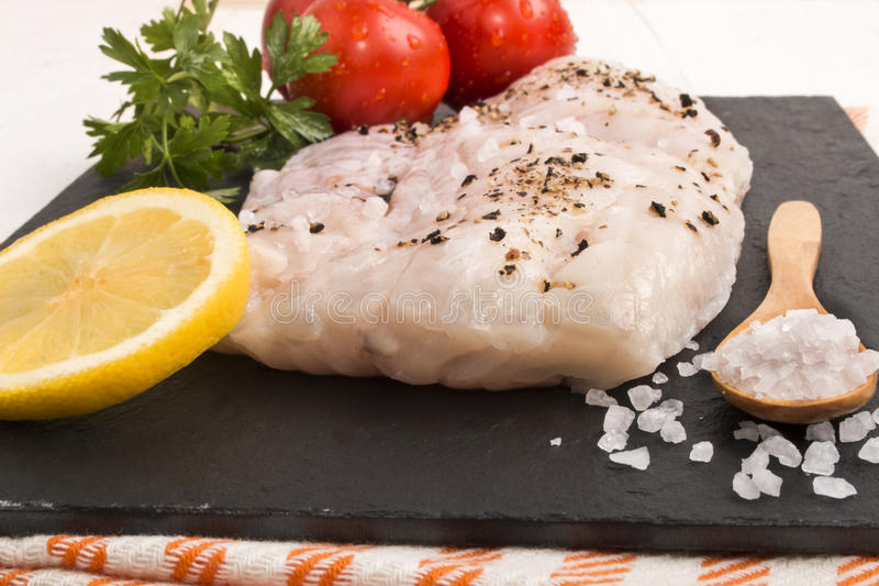 La merluza corta con la sal gruesa del mar, una rebanada de limón, perejil y fotos de archivo