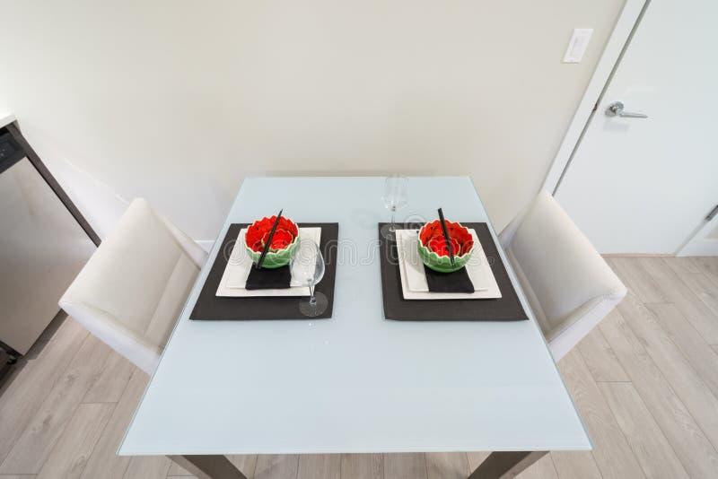 La mesa de comedor fijó para dos en una cocina moderna imagen de archivo libre de regalías