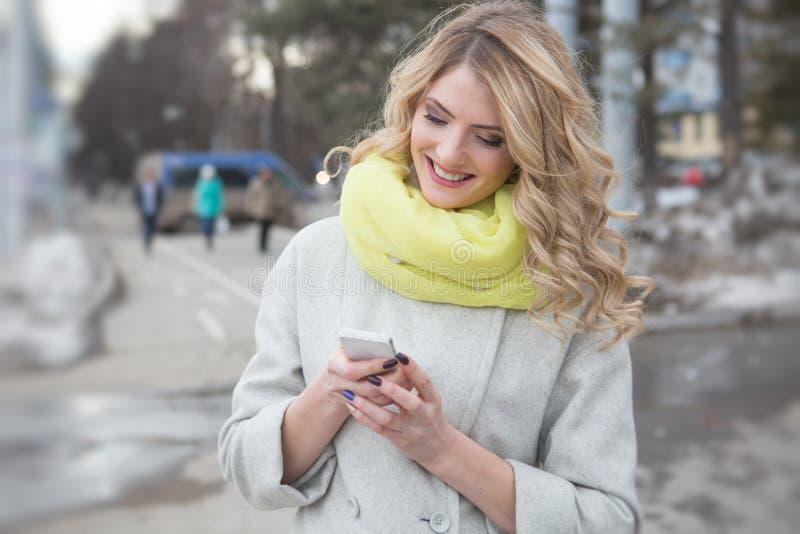 La messagerie textuelle blonde occasionnelle de sourire dehors photo stock