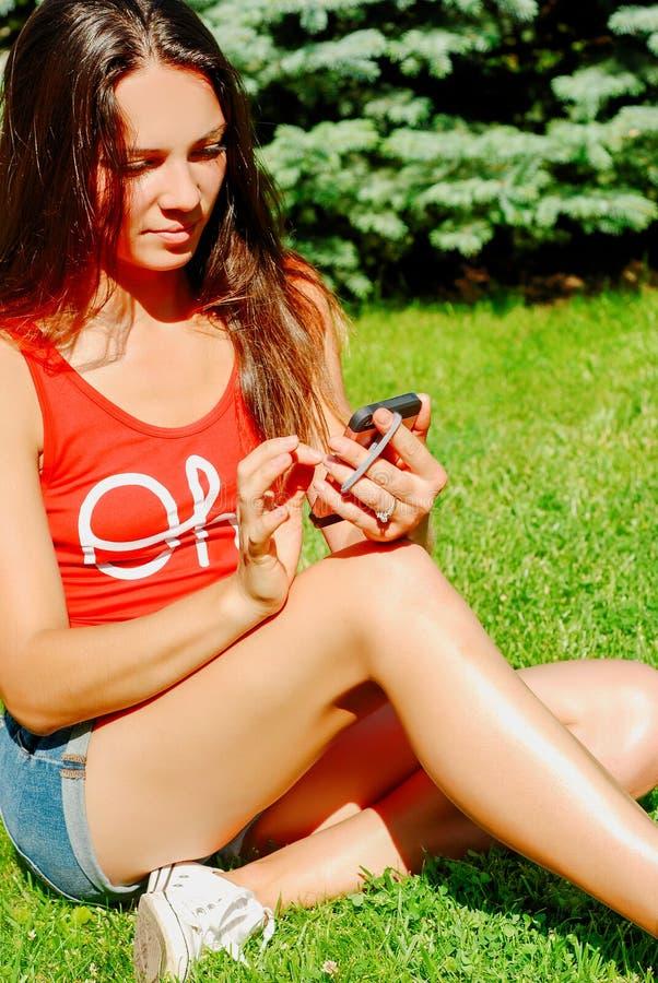 La messagerie textuelle de jeune femme tout en détendant en parc photo stock