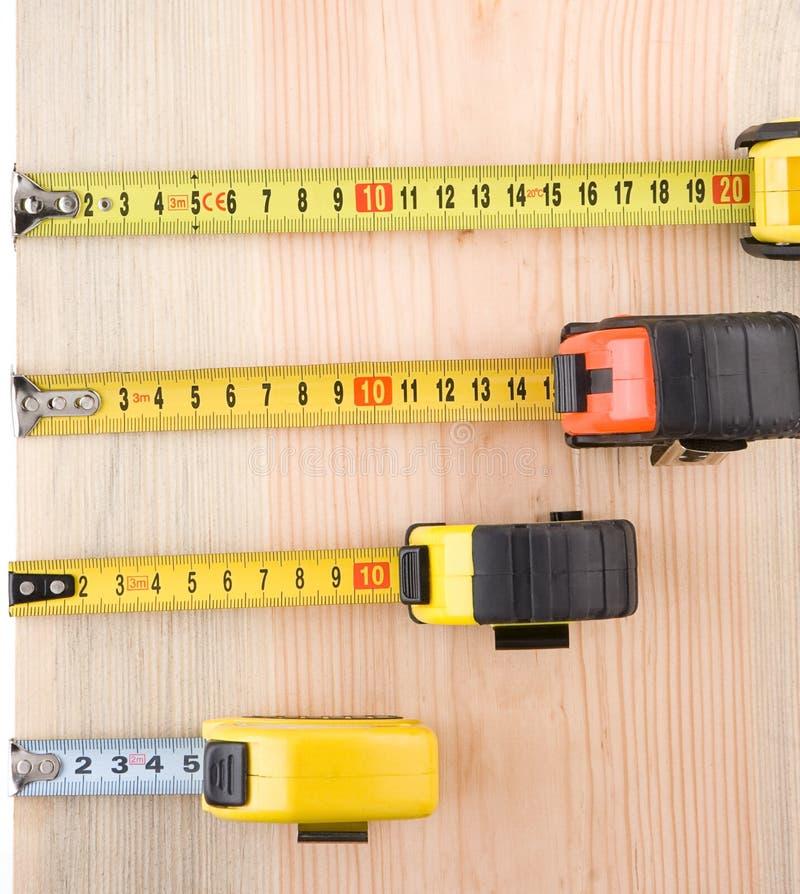 La mesure de bande sur la brique en bois solated au blanc photographie stock libre de droits