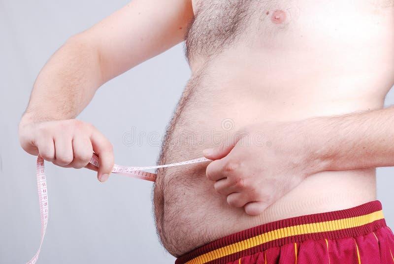 La mesure du régime d'estomac est dans l'action photographie stock