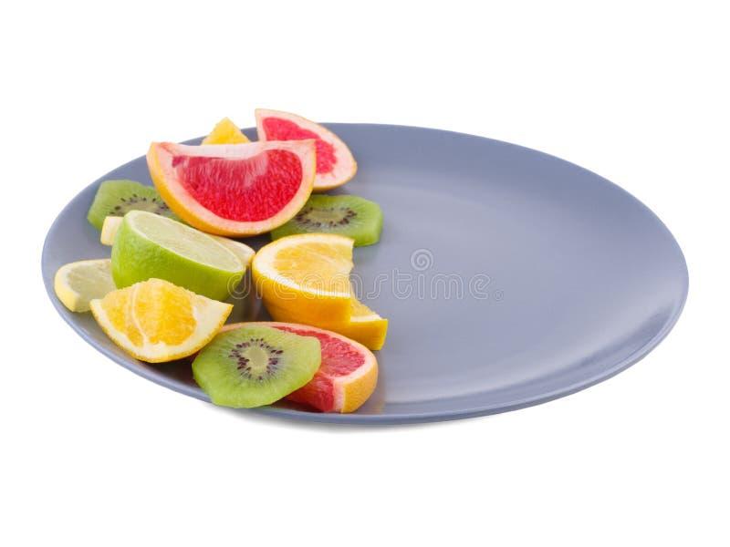 La metà del piatto è piena dei frutti tropicali vicini su su fondo isolato bianco immagini stock libere da diritti