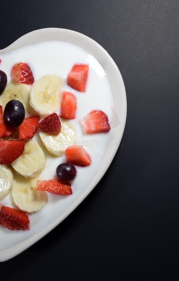 La metà del piatto crema in forma di cuore riempito di yogurt con le fette della banana, fragole incide i pezzi e le bacche dell immagini stock libere da diritti