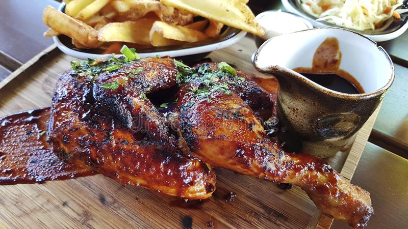 La metà del pollo fritto è servita su un vassoio di legno Su un vassoio ha fritto le patate e la salsa fotografia stock