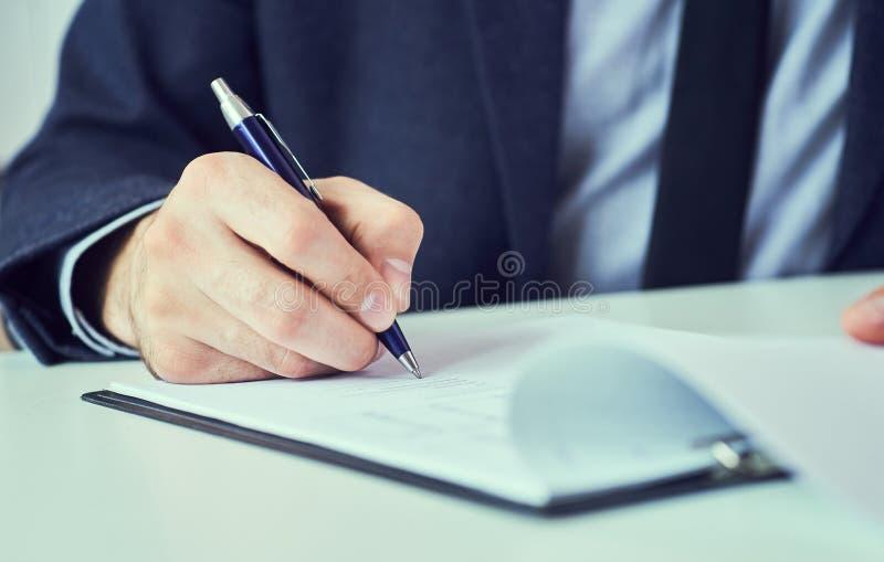 La metà di sezione dell'uomo d'affari in vestito che riempie e che firma con la forma blu di accordo di associazione della penna  fotografie stock libere da diritti