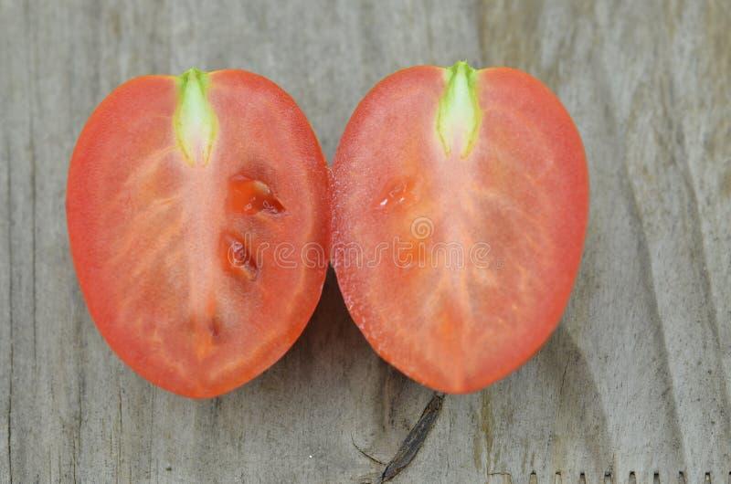 La metà fresca del taglio del pomodoro su fondo di legno, decora immagini stock