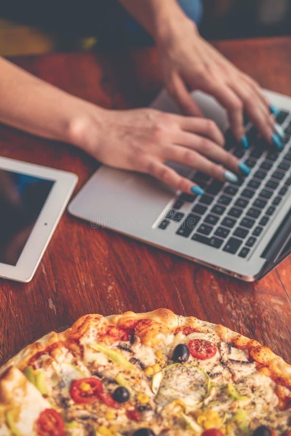 La mezcla de escritorio con los artilugios de la oficina, las fuentes y la pizza en una oficina de madera presentan el fondo Visi foto de archivo libre de regalías