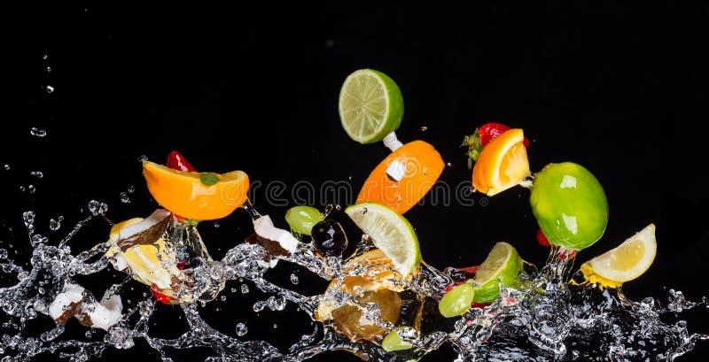 La mezcla de frutas con agua salpica en negro fotografía de archivo