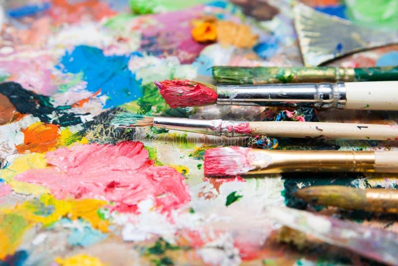 La mezcla de pinturas y las brochas se cierran para arriba imagen de archivo